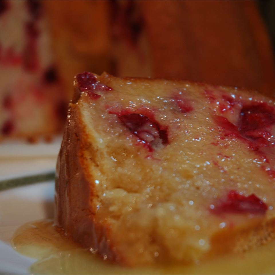 closeup of a cranberry-studded cake slice with a hot butter sauce