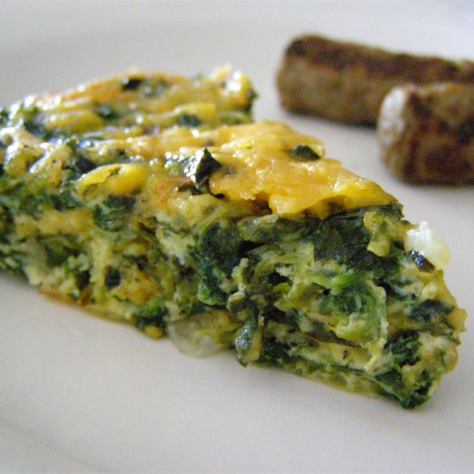 A wedge of green-flecked quiche on a white plate with two sausage links in the background