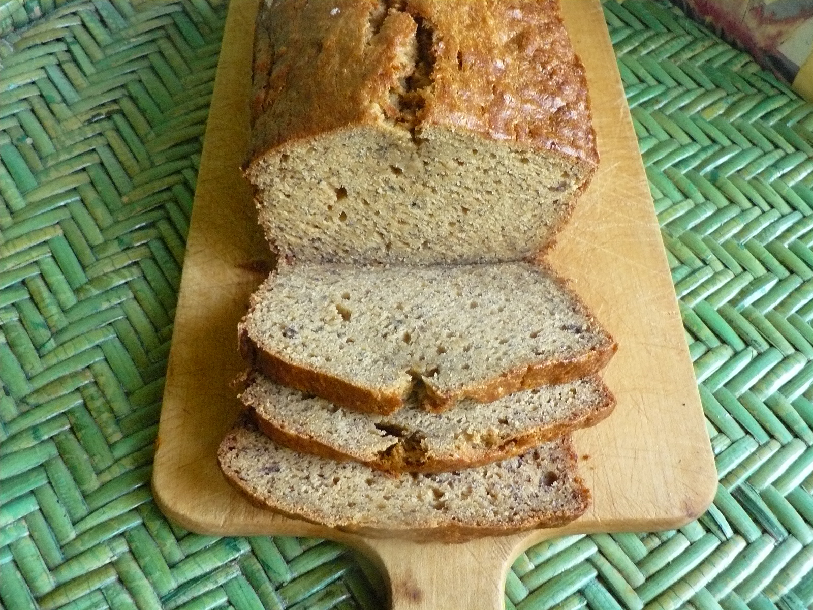 top-down view of a loaf of banana bread on a cutting board, with the first three slices cut off an end