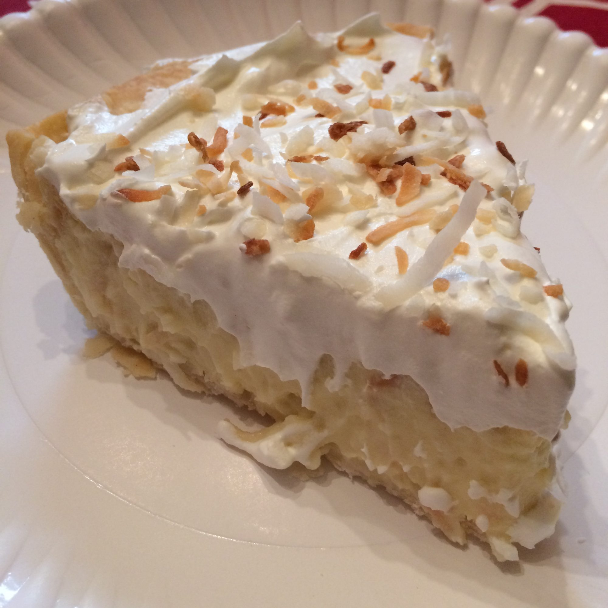 a slice of pie topped with toasted coconut on a white plate