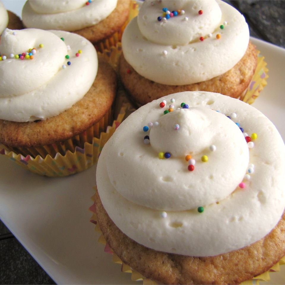 swirls of white frosting piped onto cupcakes, topped with multicolored round sprinkles