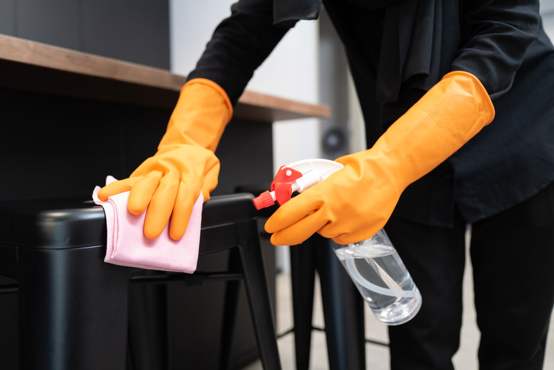 Person cleaning stool wearing gloves