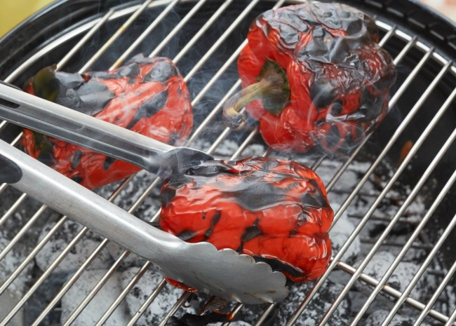Grilling red bell peppers over charcoal