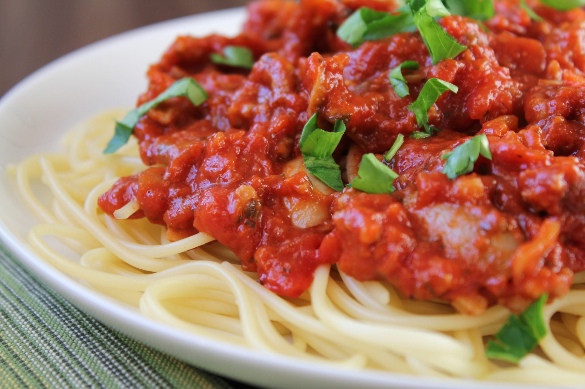 a closeup of thick tomato sauce on top of spaghetti on a white plate, garnished with chopped Italian parsley