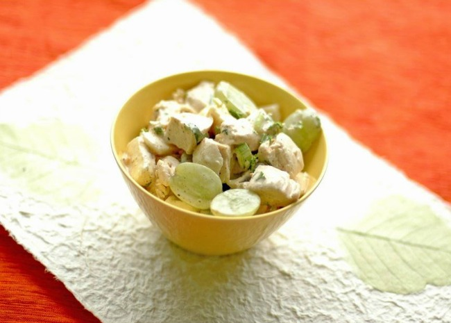 A yellow bowl filled with a creamy chicken salad with green grape halves