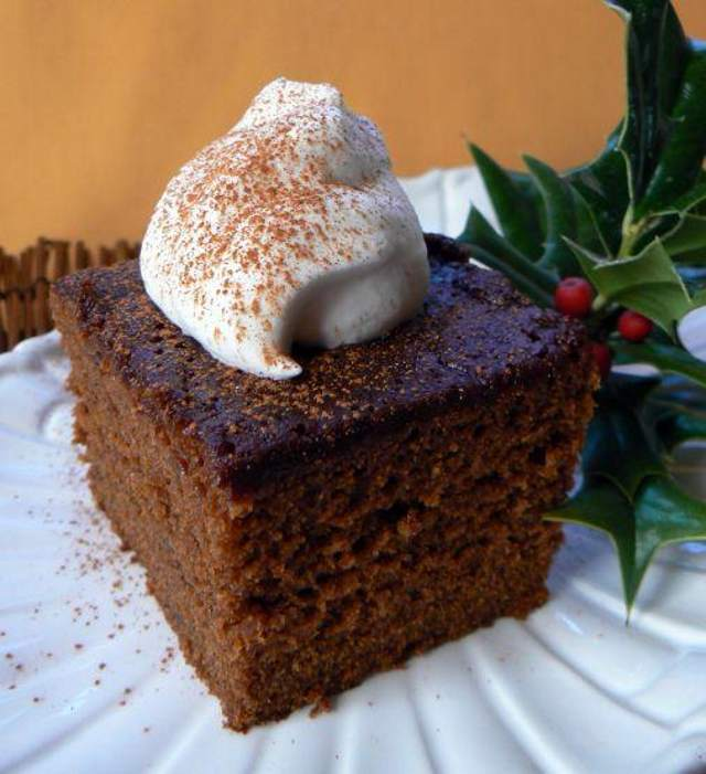 A square of gingerbread cake topped with cinnamon-dusted whipped cream on a white plate, garnished with a sprig of holly