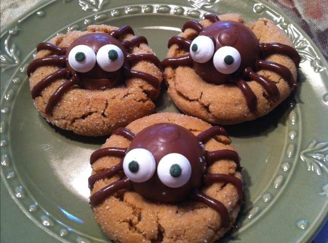 Peanut butter cookies decorated for Halloween, with candy bodies and piped chocolate legs