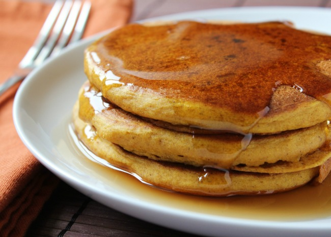 a stack of three pancakes with maple syrup on a white plate