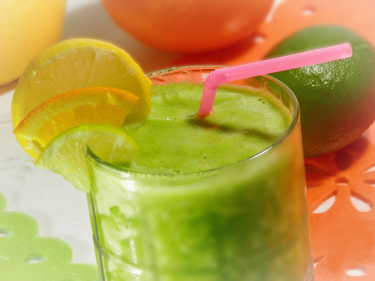 bright green smoothie with pink straw and lemon slice garnish