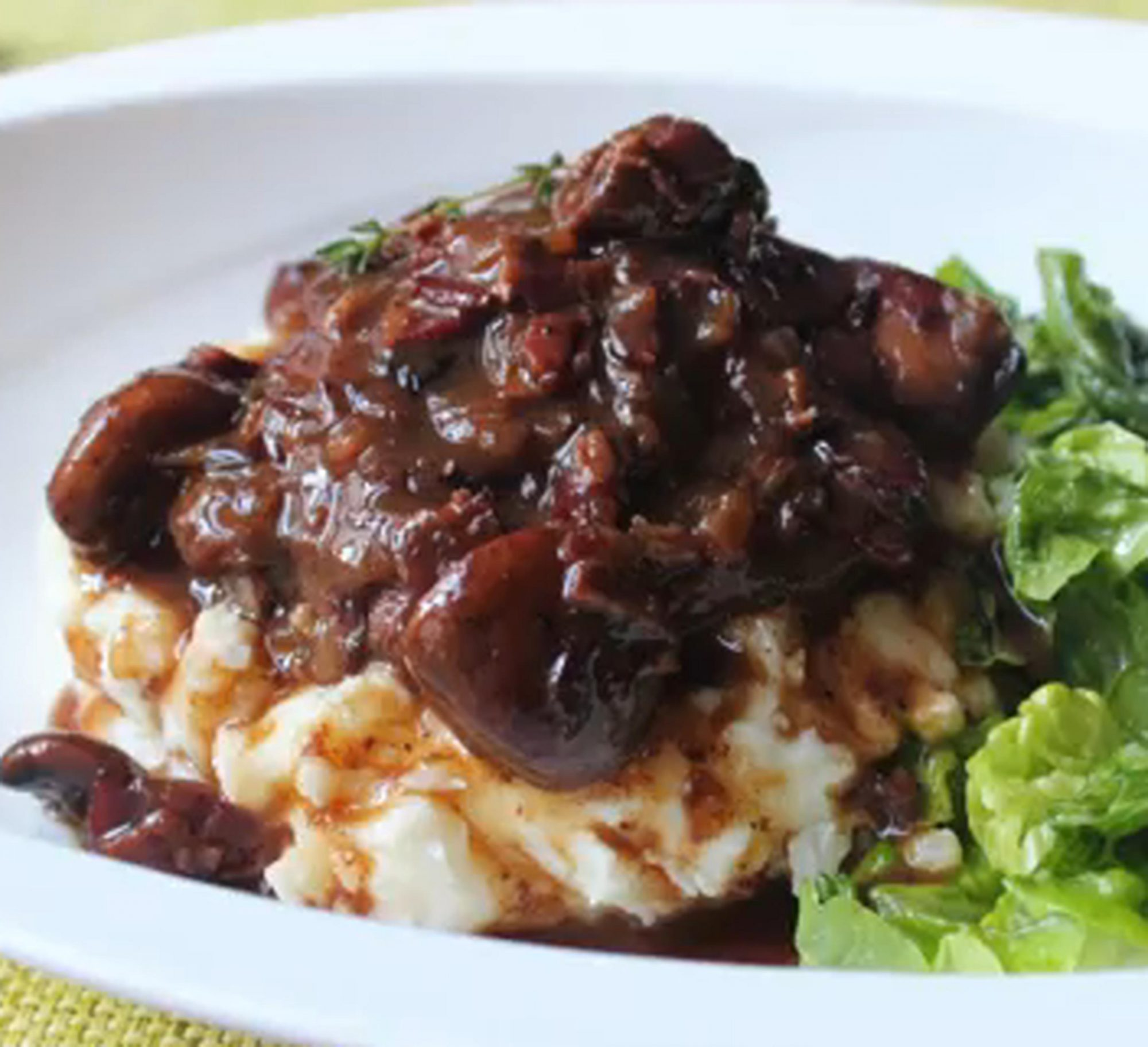 chicken and mushrooms on a bed of mashed potatoes