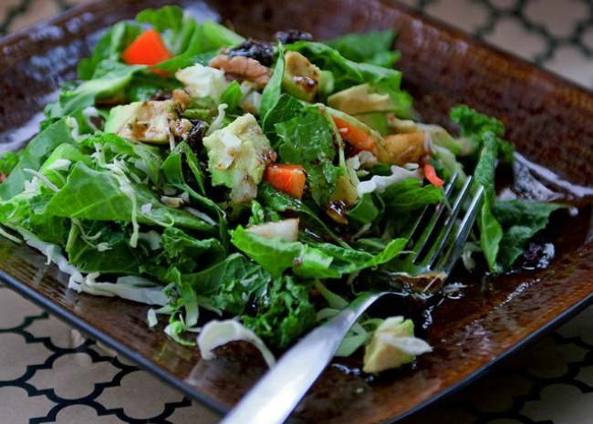 a kale and collard green salad with chopped pear, orange bell pepper, and walnuts