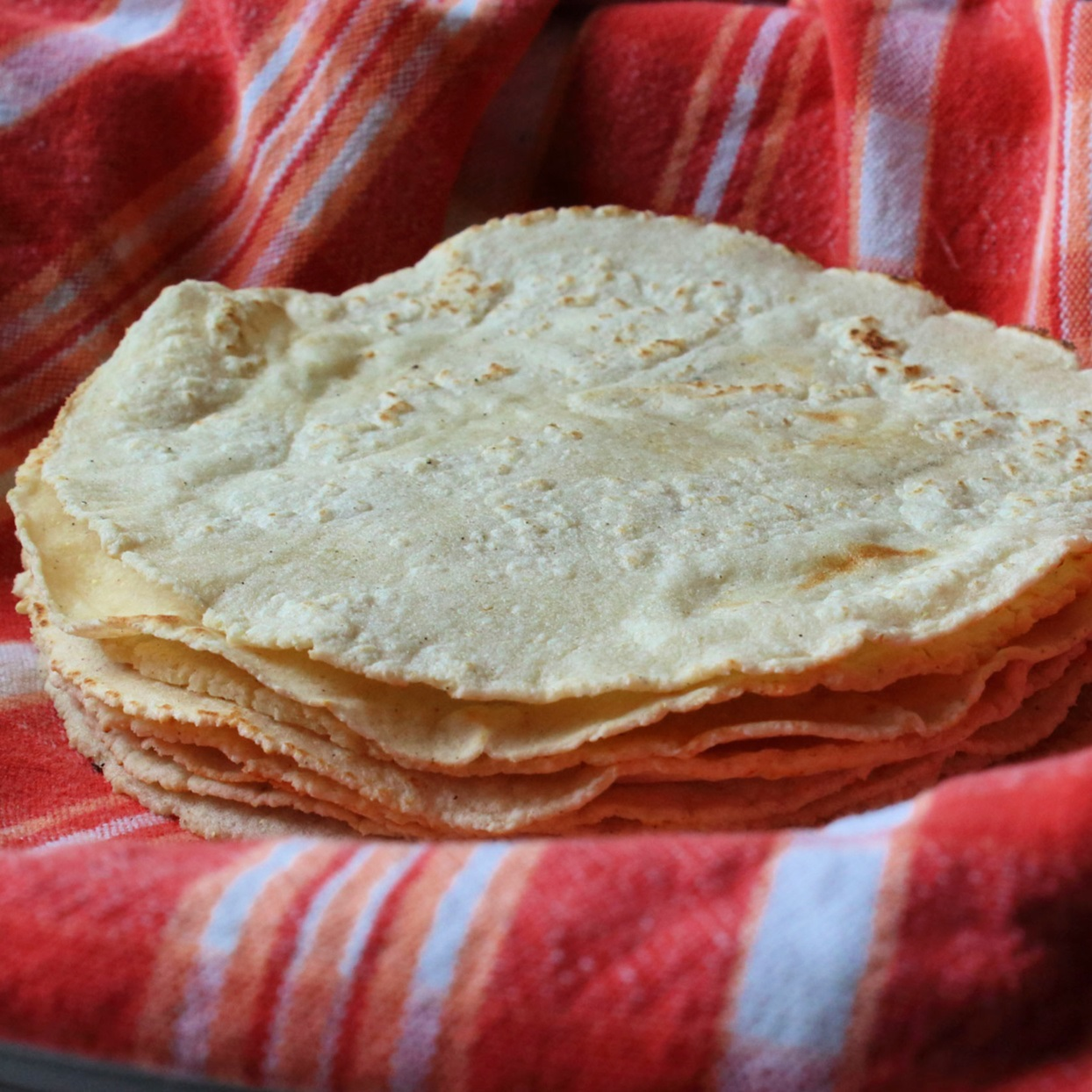 Chef John's Corn Tortillas in a bowl lined with a red striped cloth