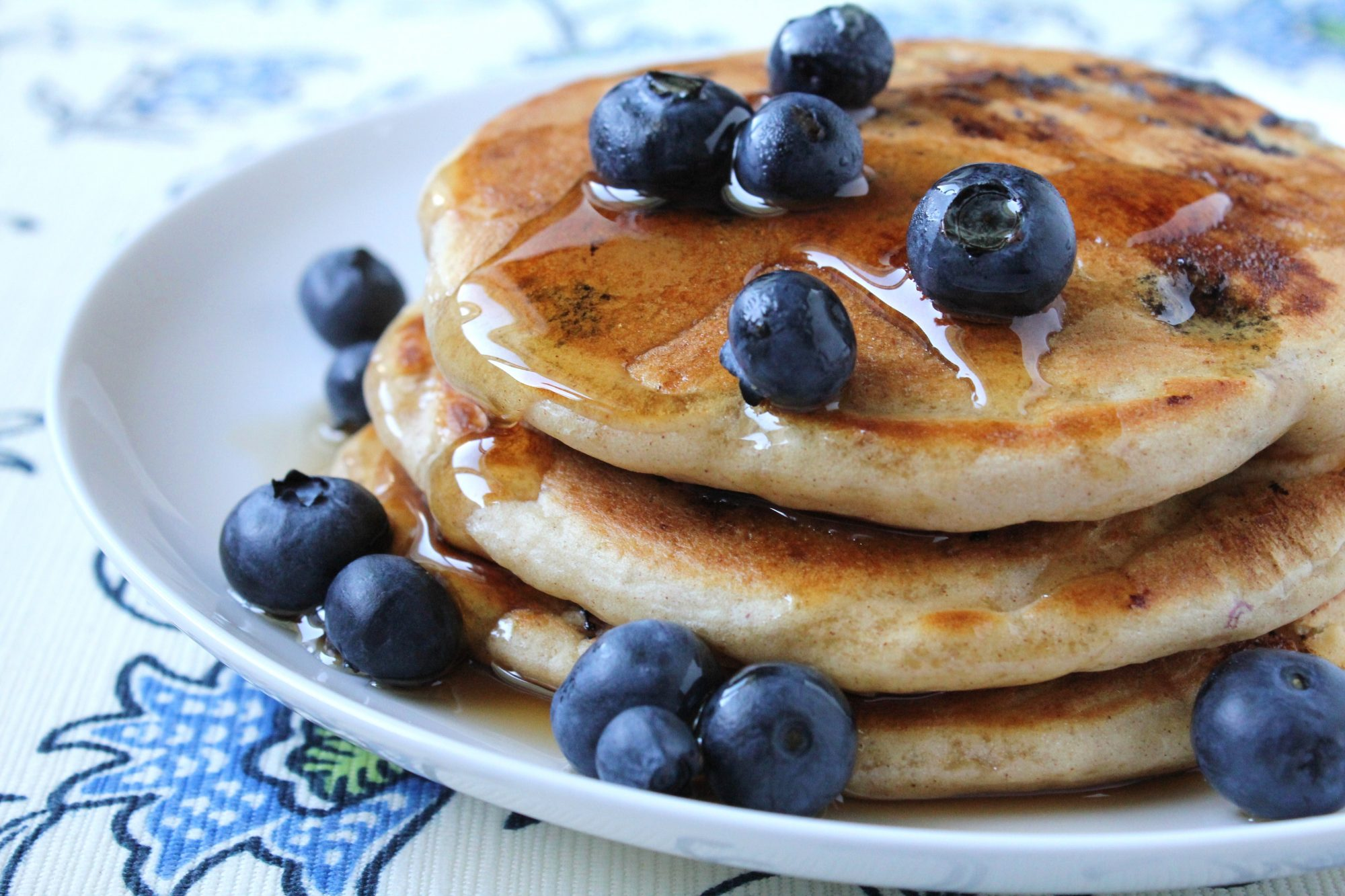 A stack of pancakes topped with fresh blueberries and maple syrup