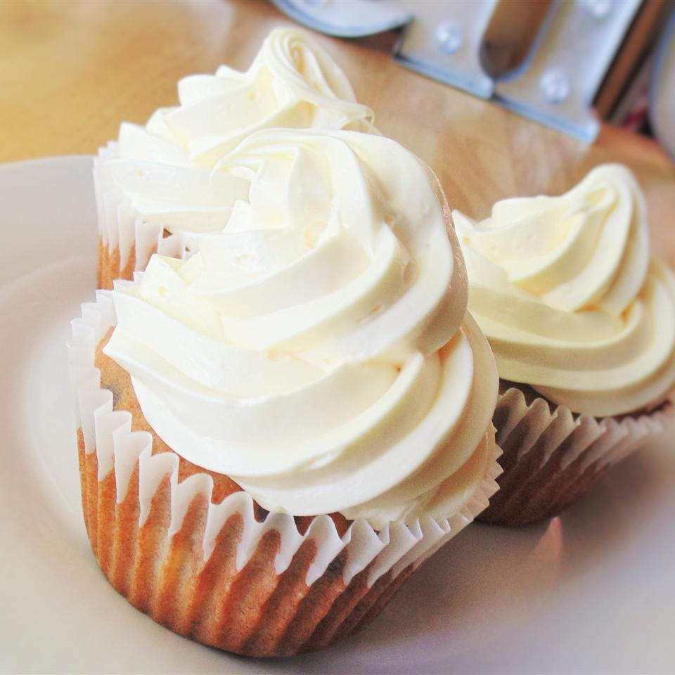 Three cupcakes with generously piped cream cheese frosting on a white plate