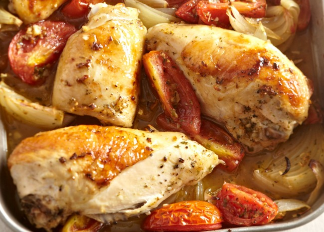 chicken breasts cooked in a baking pan with tomatoes and onions
