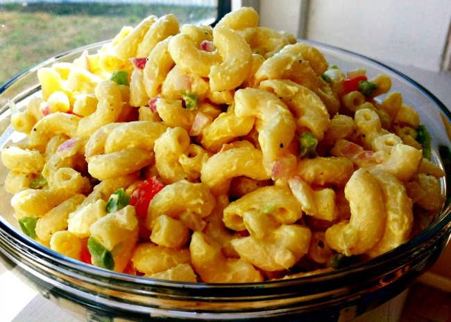 A glass bowl piled high with creamy macaroni salad