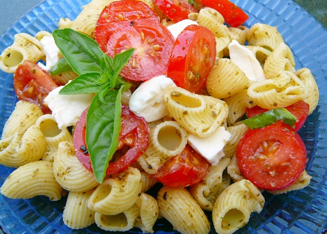 A colorful pasta salad with halved cherry tomatoes, fresh basil, and mozzarella