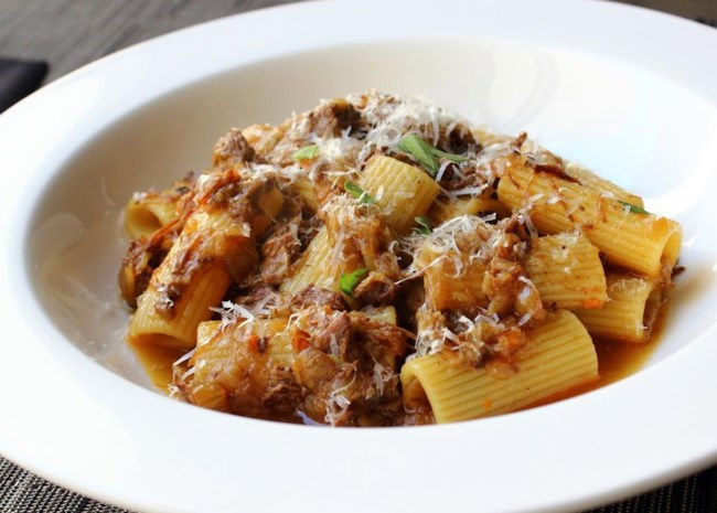 Rigatoni pasta with meat sauce topped with shredded Parmesan