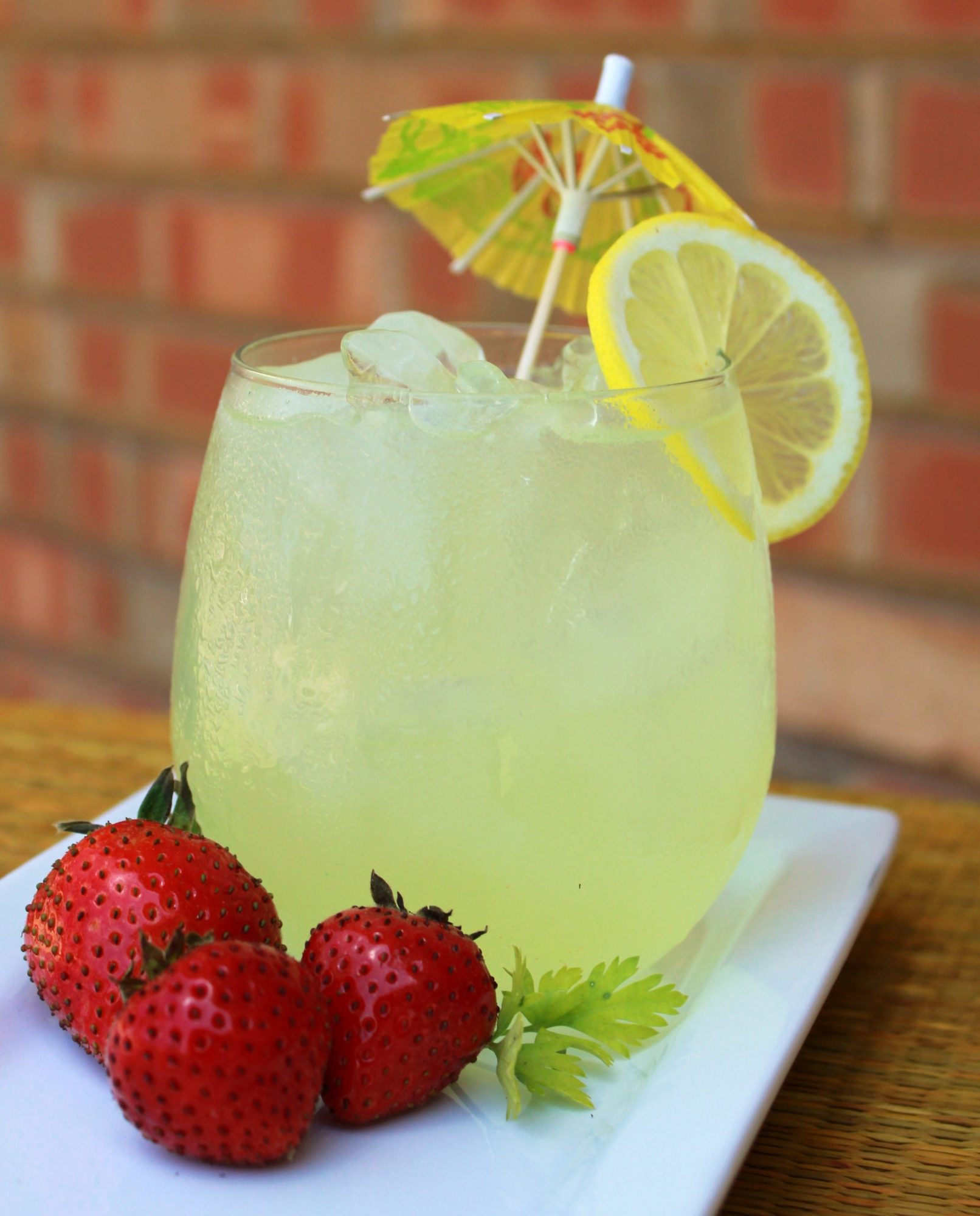 A glass of iced lemonade garnished with a yellow paper parasol and a lemon wheel, served on a white platter with three fresh strawberries