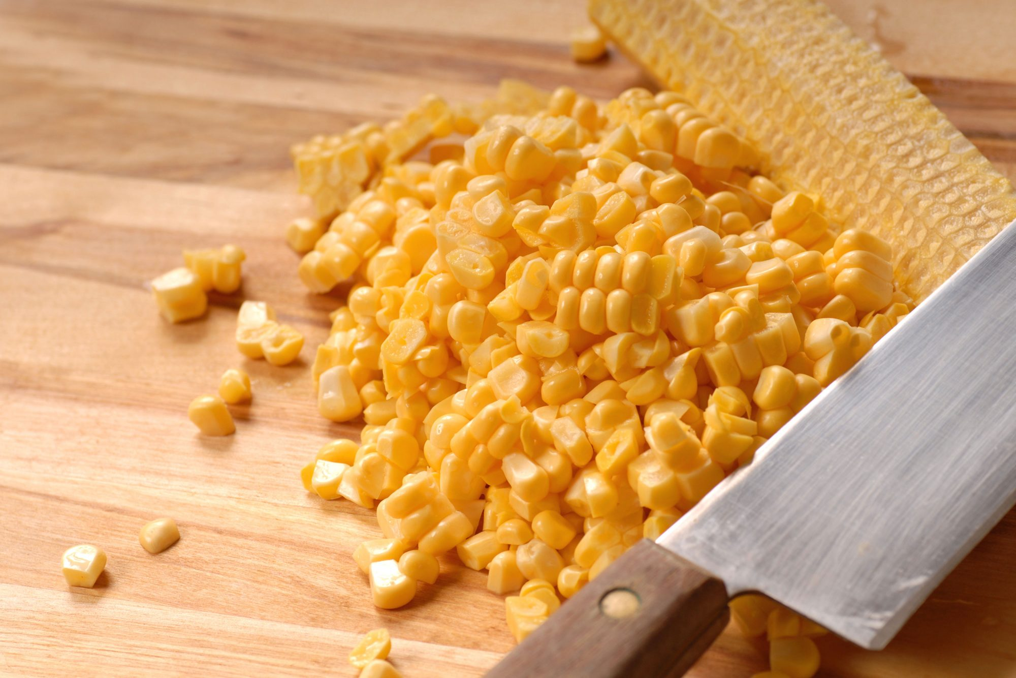 Corn removed from cob on cutting board