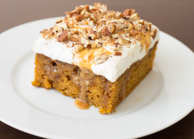 A slice of pumpkin cake topped with whipped cream and chopped pecans, drizzled with caramel sauce