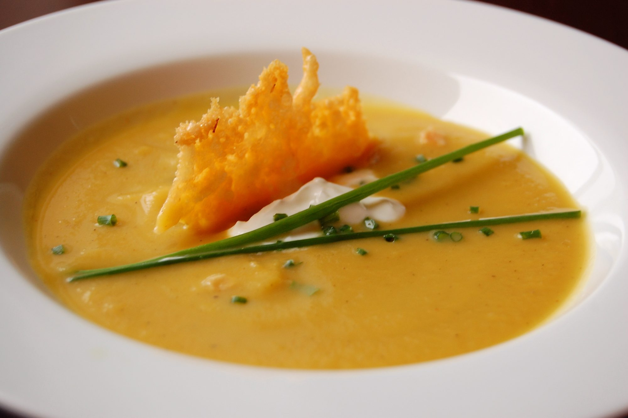 closeup of thick golden soup in a white bowl with garnishes