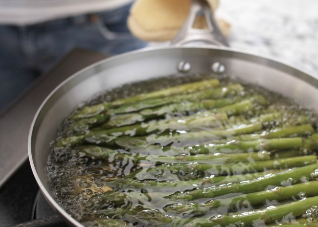 boiling asparagus in a skillet on a stovetop