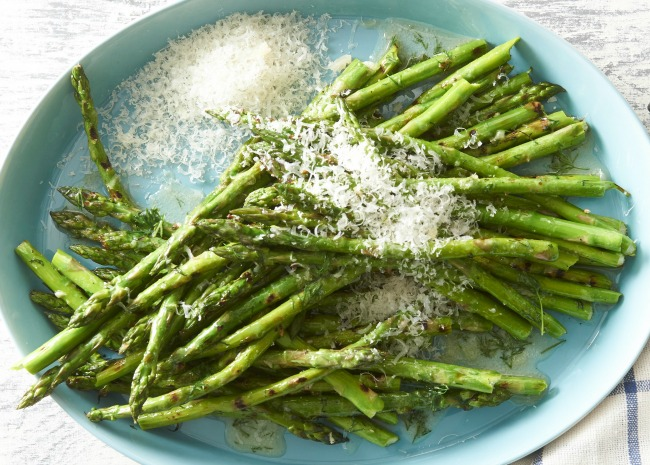 grilled asparagus topped with grated Parmesan cheese on a blue plate