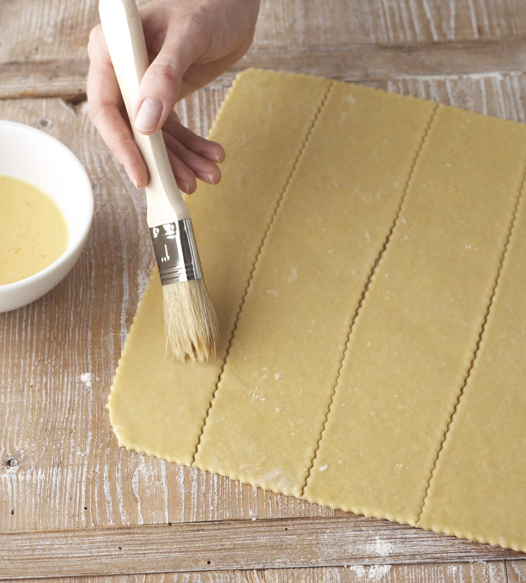 brushing strips of pasta with egg wash