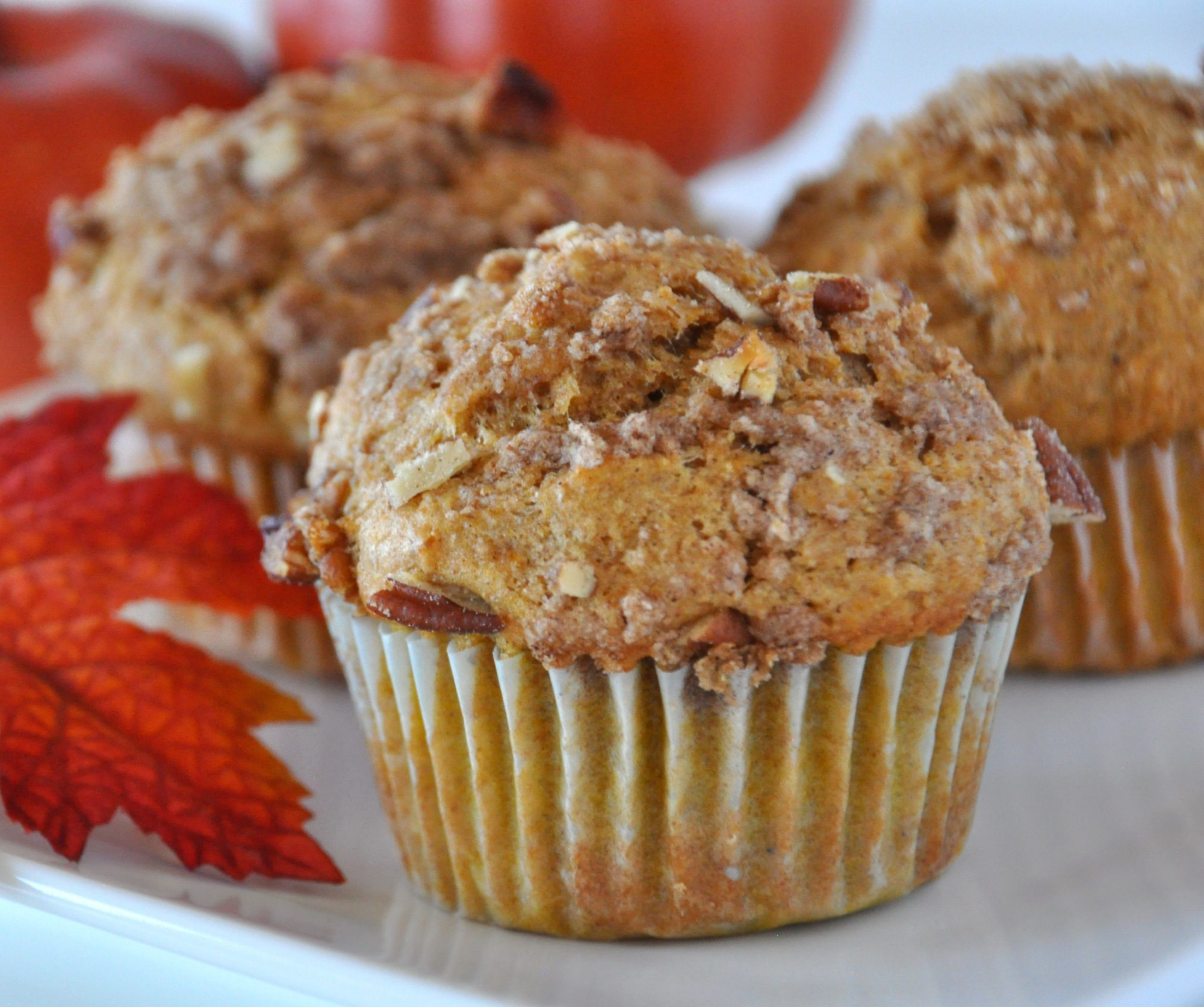 a closeup of nut-topped muffins with fall leaf decor