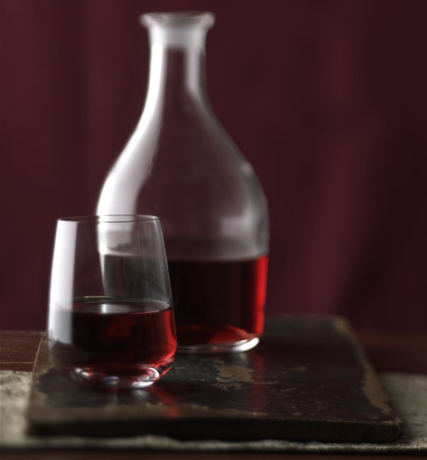 Red glass with carafe on cutting board