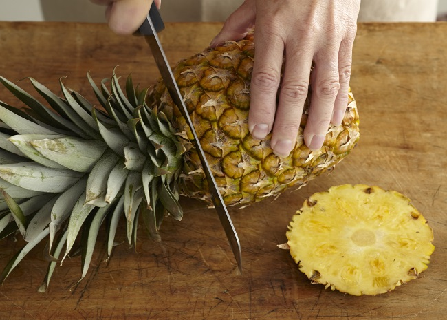 Slicing Off Both Ends of a Pineapple