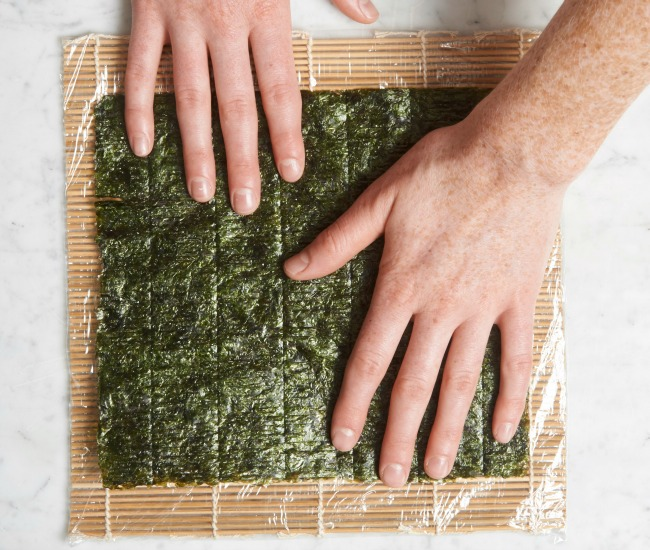 Laying nori on plastic wrap on bamboo mat