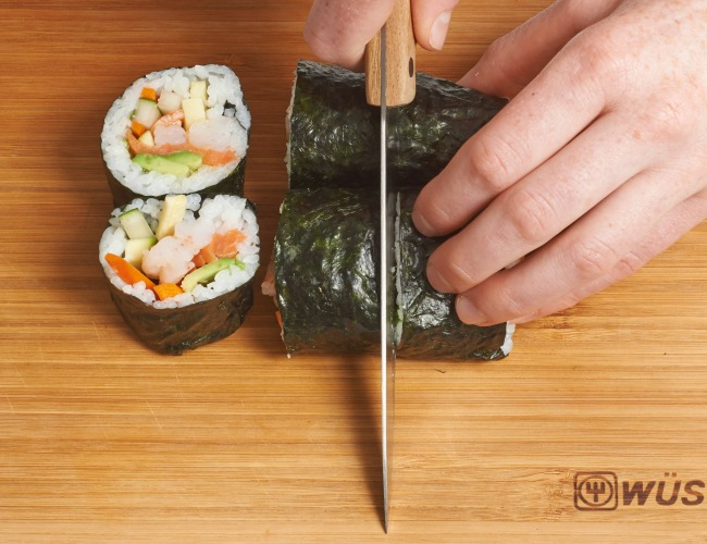 Cutting a roll of Sushi