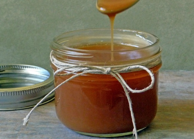 A decorative jar of caramel sauce tied with string, with a spoon drizzling sauce