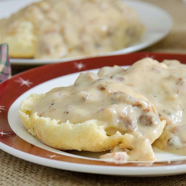 A red-rimmed plate with a split biscuit topped with sausage gravy