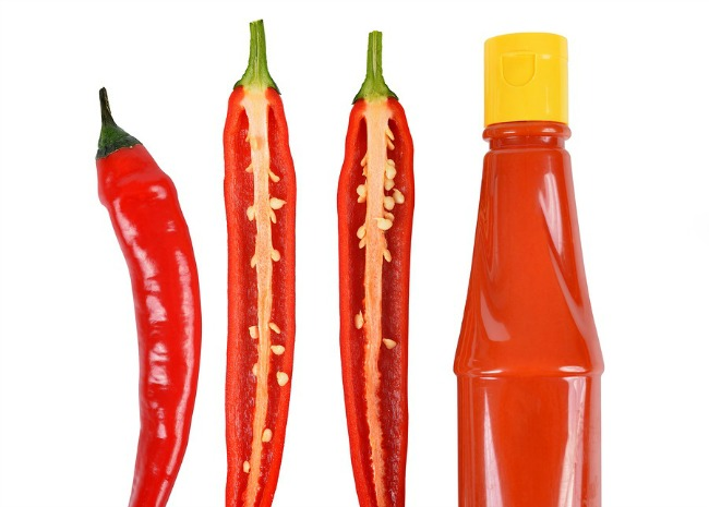 Hot sauce in bottle with Red chili pepper isolated on white