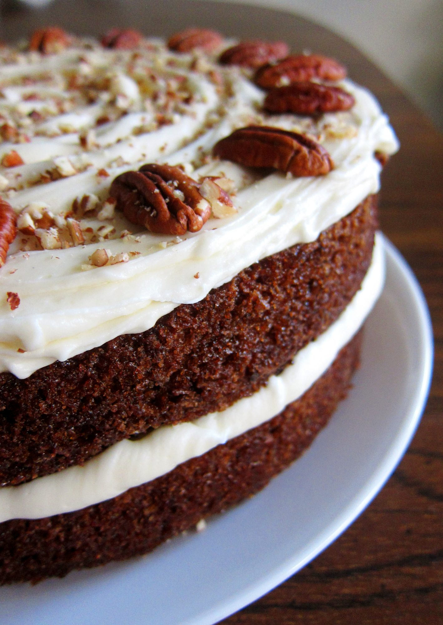 side view of a cake with frosting between two layers and on top, garnished with pecan halves and chopped pecans