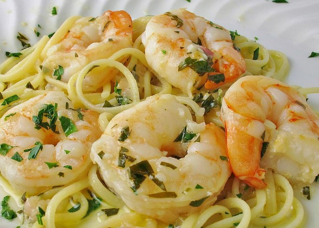 closeup of herb-topped shrimp on a bed of spaghetti