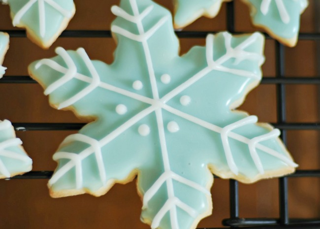 closeup of a snowflake-shaped cookie decorated with pale blue icing and piped white details