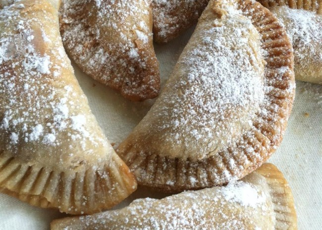 fried apple pies dusted with confectioners' sugar