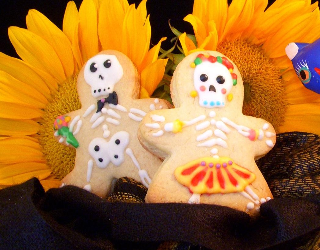 Sugar cookies cut out in gingerbread boy and girl shapes, decorated as Day of the Dead skeletons