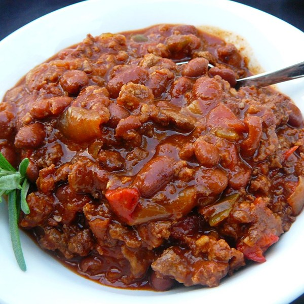 A bowl of beef and sausage chili with beans, garnished with a sprig of rosemary
