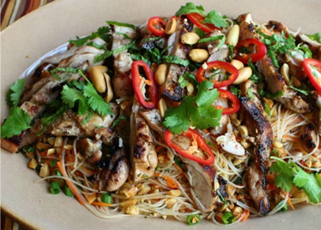 top-down view of grilled chicken strips on a bed of noodles, garnished with cilantro, red pepper rings, and peanuts