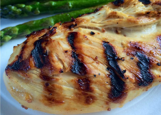 closeup of a boneless skinless chicken breast with grill marks