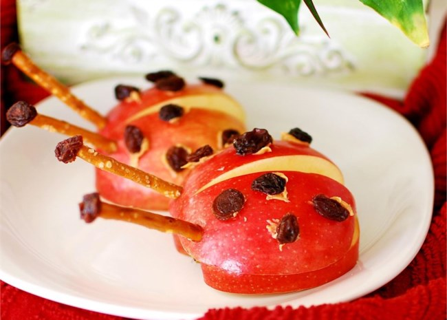"""Apple halves topped with dots of peanut butter """"glue"""" and raisin spots, with pretzel stick antennae"""