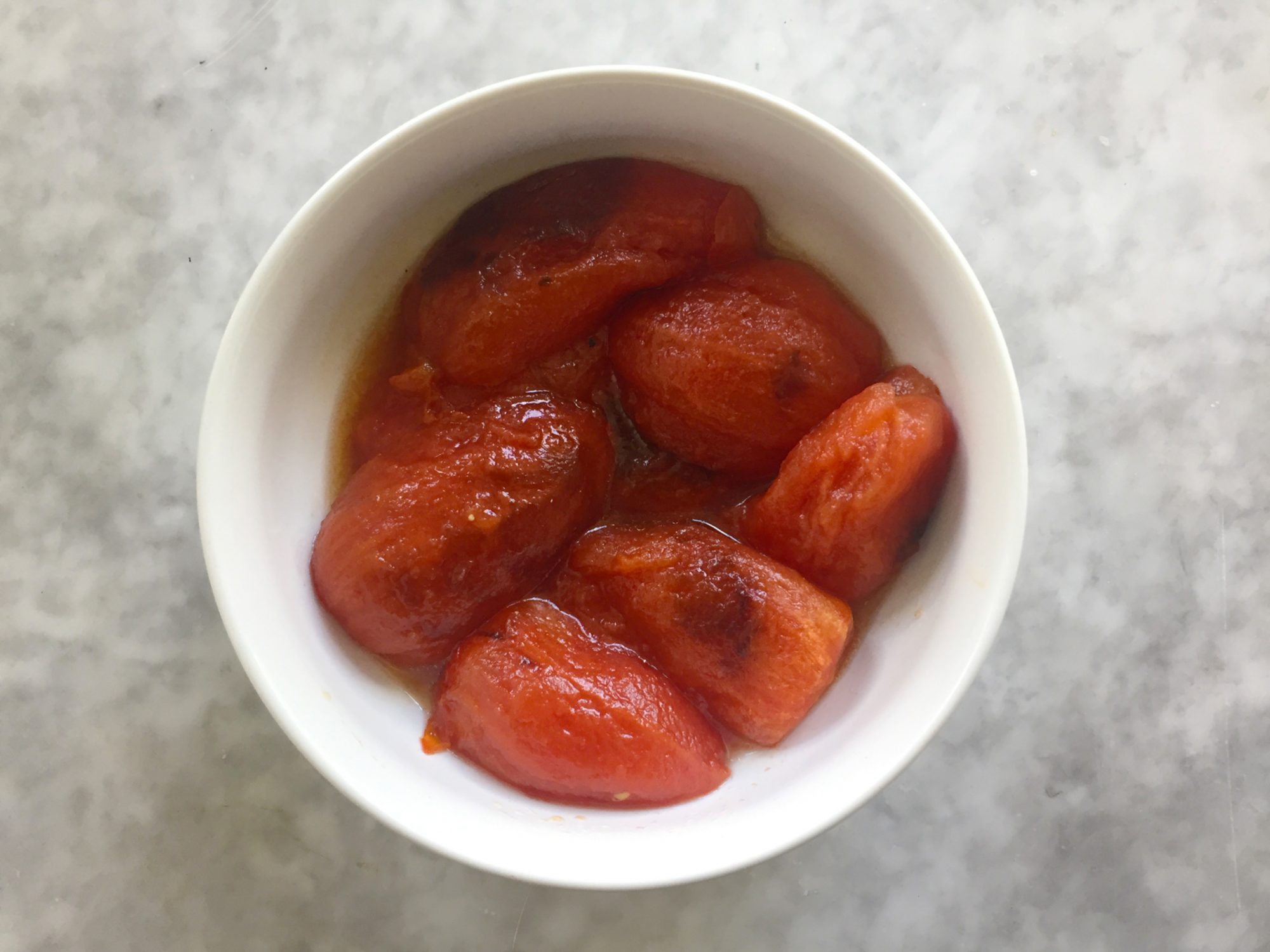 Fire-roasted tomatoes without skins in bowls.