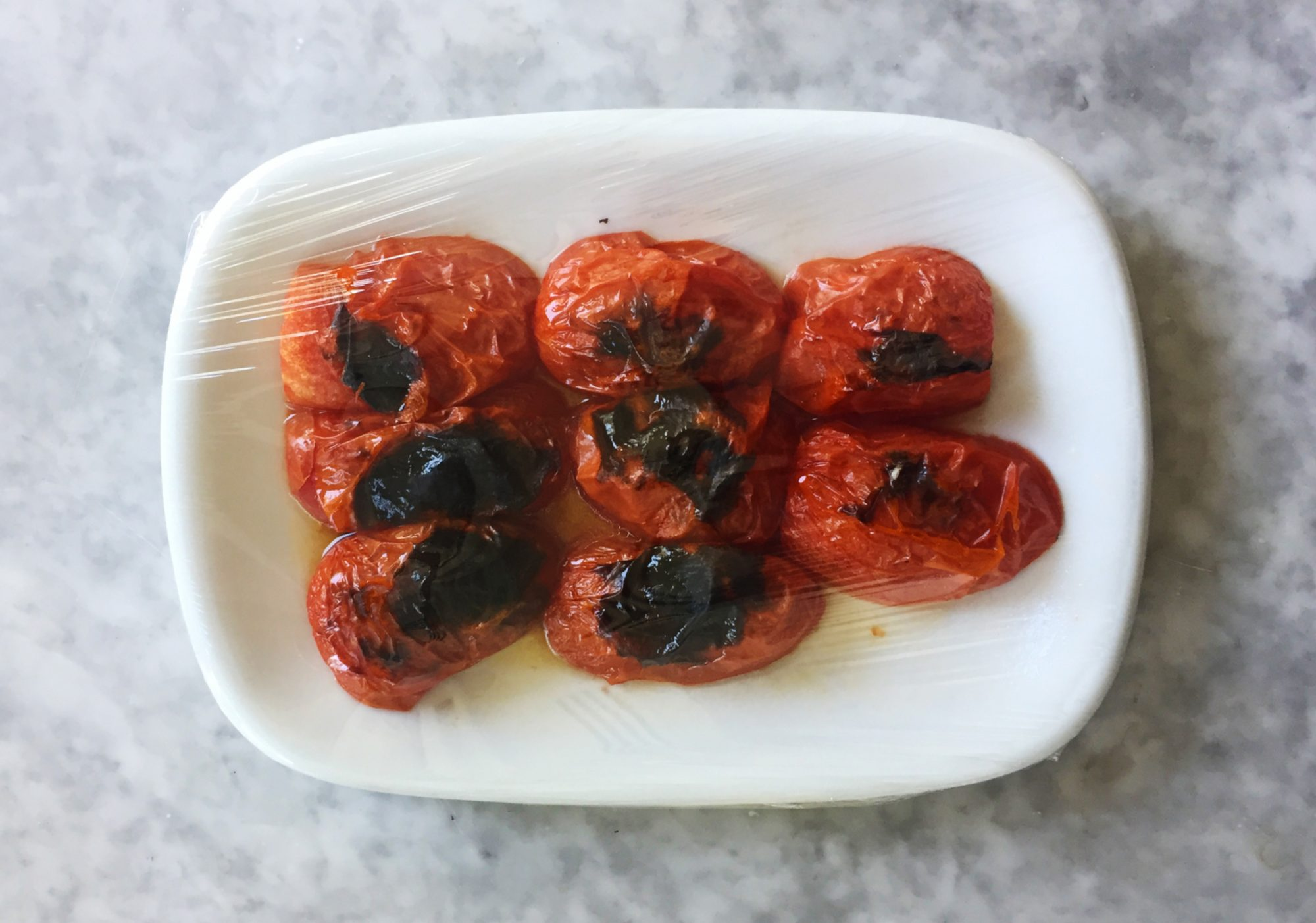 Fire-roasted tomatoes on plate with plastic wrap.