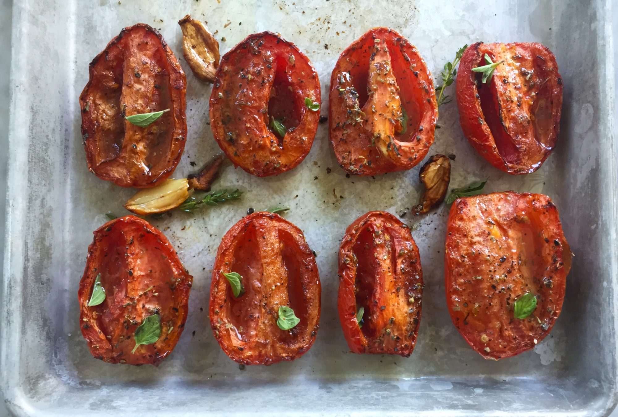 Roasted roma tomatoes on a sheet tray.