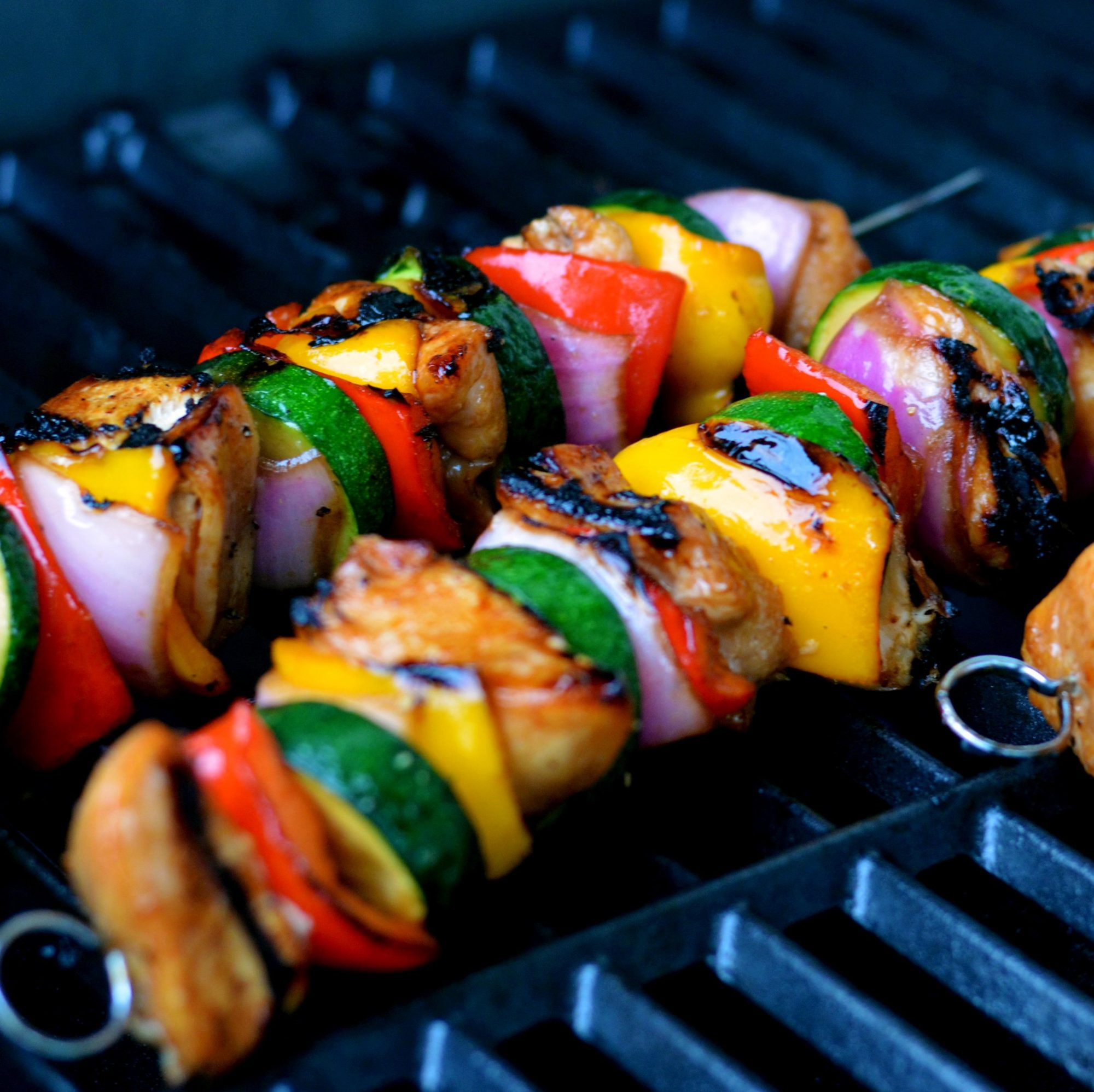 two colorful skewers of chicken, red bell pepper, zucchini, red onion, and yellow squash on a grill